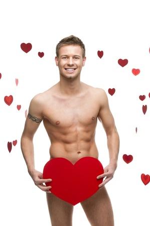 homme nu: jeune joyeux caucasien homme dr�le nu tenant coeur CBIG papier rouge isol� sur fond blanc avec la chute des coeurs rouges Banque d'images