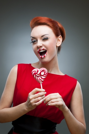 young winking caucasian red-haired woman in red dress holding lollipop with funny expression Stock Photo