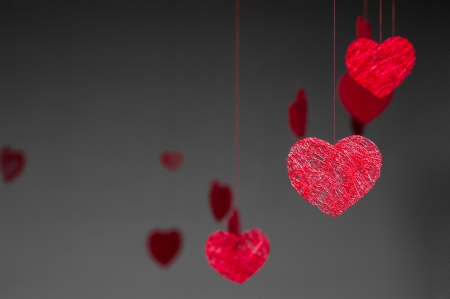 suspend: red paper hearts dangling on red threads over dark gray background