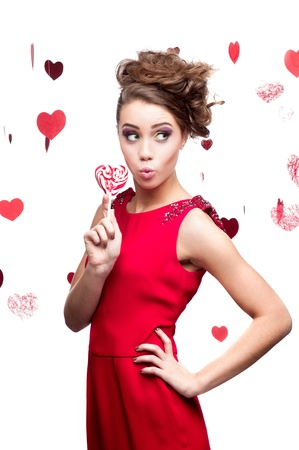 young cheerful surprised caucasian brunette woman in red dress holding lollipop Stock Photo