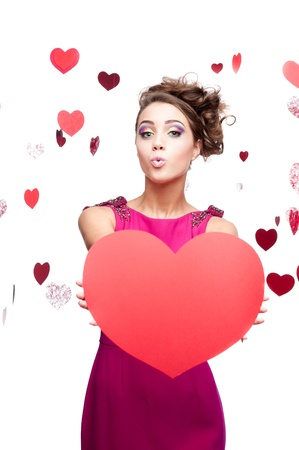 young cheerful caucasian brunette woman in red dress holding big red paper heart Stock Photo