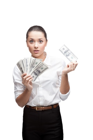 young cheerful caucasian brunette businesswoman in white blouse holding money with surprised expression isolated on white