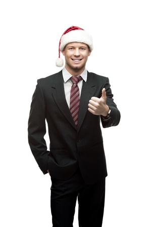 young smiling caucasian businessman in black suit and santa hat isoalted on white 免版税图像
