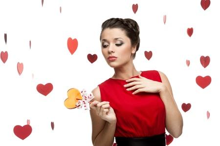 giovane donna sexy caucasica bruna in rosso vestito azienda lecca-lecca