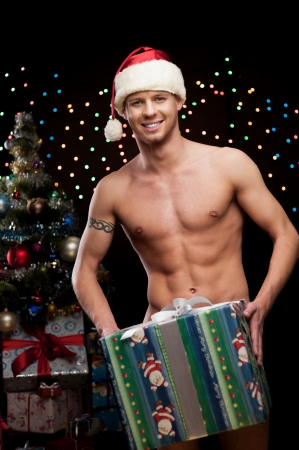 young naked man in santa hat holding big christmas gift over christmas tree and lights on background