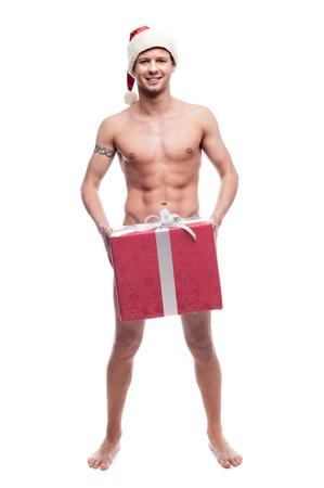 homme nu: jeune homme nu dans le chapeau de Santa tenue rouge grand cadeau de Noël sexy et regardant la caméra isolée sur fond blanc