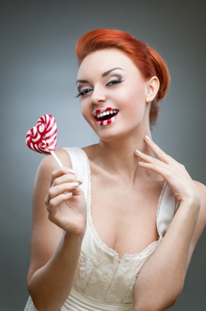 young smiling caucasian red-haired woman in white dress holding lollipop over gray background Stock Photo - 16536884