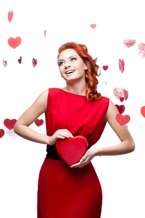 young smiling red-haired caucasian woman in red dress holding red heart isolated on white photo