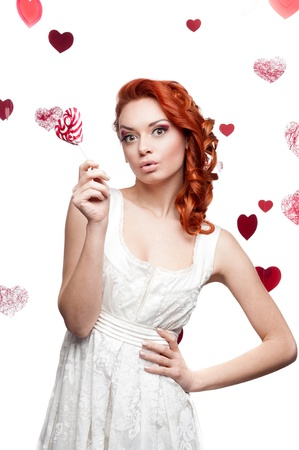 young cheerful caucasian red-haired woman holding lollipop photo