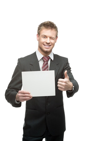 thumbup: cheerful winking caucasian businessman in gray suit holding sign and showing thumb-up isolated on white background