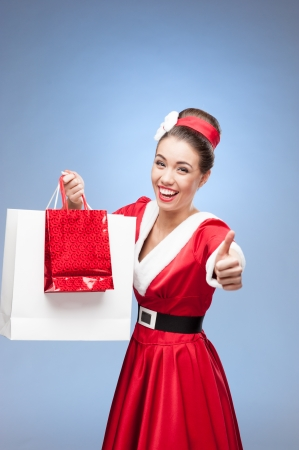 young cheerful retro girl in red vintage dress holding shopping bags Stock Photo - 16929520