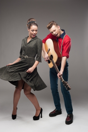 cheerful young caucasian guitar player and dancing girl in vintage clothing over gray background photo
