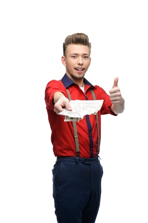 cheerful young caucasian man in red vintage clothing holding money and showing thumb ub photo