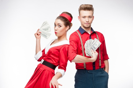 cheerful young caucasian couple in red vintage clothing holding money isolated on white photo