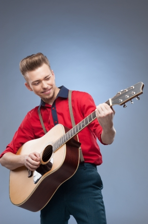caucasian young vintage man in red shirt playing guitar over blue background photo