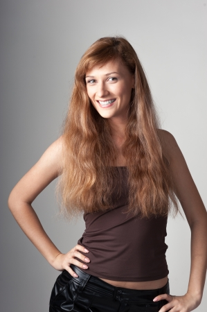cheerful happy casual caucasian girl with long brown hair on gray background