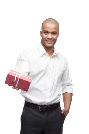 giovane uomo nero sorridente che tiene regalo rosso isolato su bianco