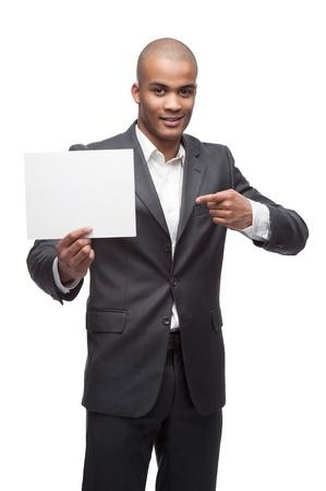 jungen fr�hlichen schwarzen Gesch�ftsmann h�lt und zeigt auf Zeichen auf wei�em isoliert