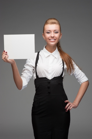 young cheerful caucasian businesswoman holding sign isolated on white photo