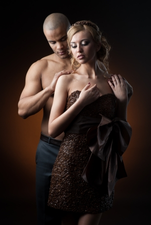 young sensual caucasian woman in dress made of coffee beans and black man standing over gradient orange background