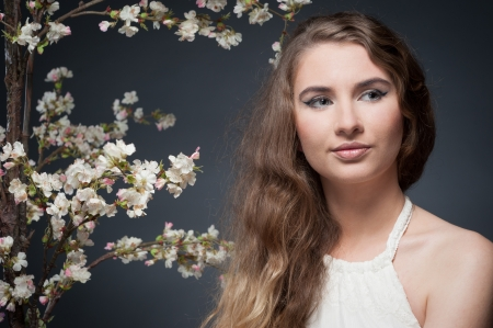 sensual caucasian woman in white dress near flowering tree over gray background Stock Photo - 18626916