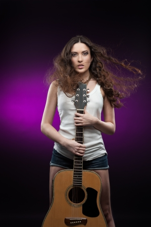 young casual sexy brunette woman in white t-shirt with windy hair holding guitar while standing over purple background photo