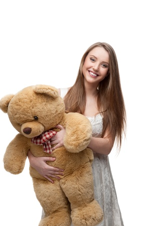 young cheerful caucasian girl in short white dress holding big soft toy bear isoalted on white photo