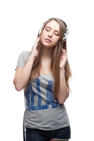 young casual caucasian girl with headphones listening to music isolated on white photo