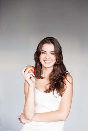 white singlet: young smiling casual caucasian brunette  woman in white singlet holding red apple over gray background Stock Photo
