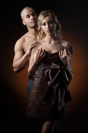 caucasica giovane donna sensuale in abito fatto di chicchi di caff? e l'uomo nero in piedi su sfondo sfumato arancio