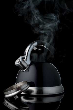 black kettle with chrome plated details and steaming neck on black background photo