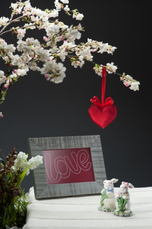 white flowering tree with red heart and photo frame near two rabbit statuette on table over gray background photo