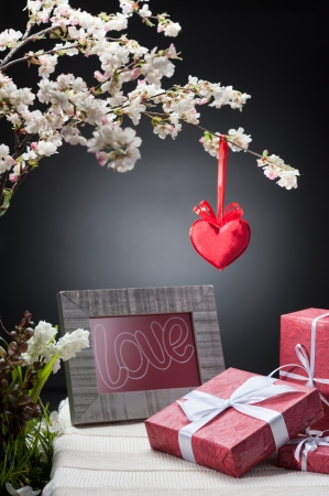 white flowering tree with red heart and photo frame near three red gifts on table over gray background photo