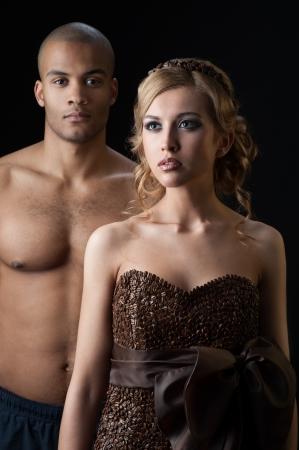 junge sinnliche caucasian Frau im Kleid von Kaffeebohnen und schwarze Mann, der �ber Gradienten orange Hintergrund gemacht