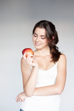 white singlet: beatiful caucasian thoughtful young woman  in white singlet holding red apple over gray background Stock Photo
