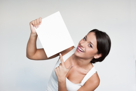 cheerful young woman in white singlett holding and pointing on sign over gray background Stock Photo