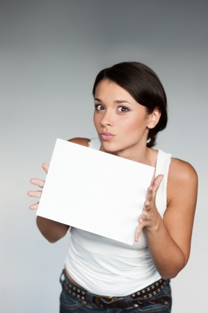 cheerful young woman in white singlett holding sign over gray background photo