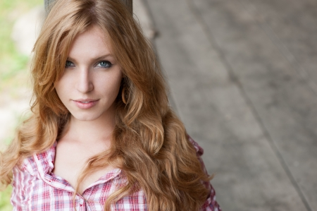outdoors portrait of beautiful red haired  caucasian young woman photo