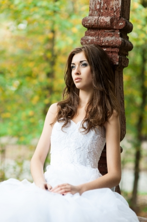 outdoors portrait of beautiful young caucasian brunette woman in white wedding dress over green foliage on background Stock Photo - 18793615