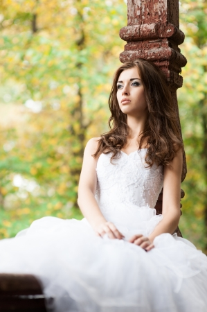 outdoors portrait of beautiful young caucasian brunette woman in white wedding dress over green foliage on background Stock Photo - 18793613