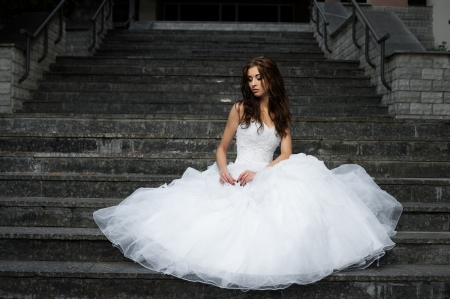 outdoors portrait of beautiful young caucasian brunette woman in white wedding dress over gray stairs on background Stock Photo - 18793610