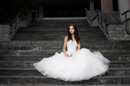 outdoors portrait of beautiful young caucasian brunette woman in white wedding dress over gray stairs on background Stock Photo - 18793607