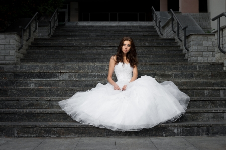 outdoors portrait of beautiful young caucasian brunette woman in white wedding dress over gray stairs on background Stock Photo