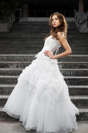 outdoors portrait of beautiful young caucasian brunette woman in white wedding dress over gray stairs on background Stock Photo - 18793602