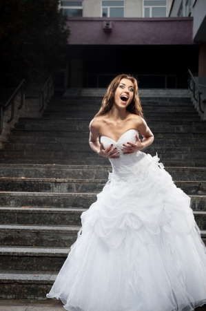 outdoors portrait of beautiful young caucasian brunette woman in white wedding dress over gray stairs on background Stock Photo - 18918618