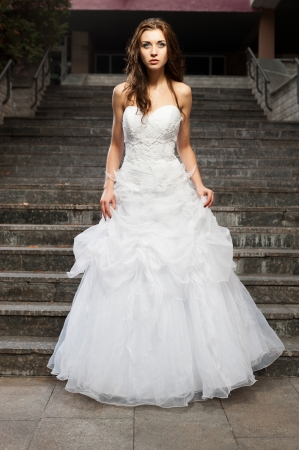 outdoors portrait of beautiful young caucasian brunette woman in white wedding dress over gray stairs on background Stock Photo - 18793606