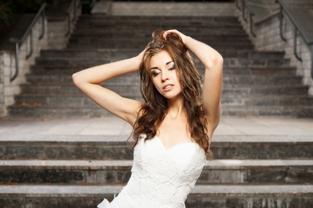 outdoors portrait of beautiful young caucasian brunette woman in white wedding dress over gray stairs on background Stock Photo - 18865905