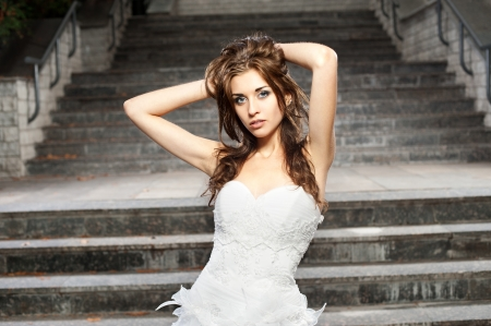 outdoors portrait of beautiful young caucasian brunette woman in white wedding dress over gray stairs on background Stock Photo - 18865926