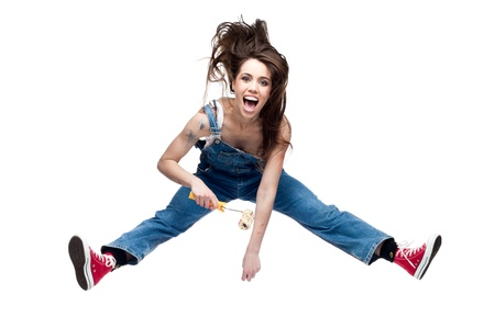 beautiful young caucasian woman artist in blue jeans jumping and screaming isolated on white background