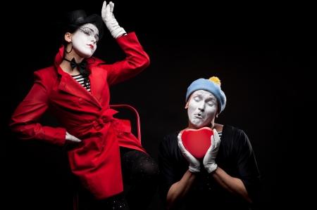 due mimi divertenti che tengono cuore rosso isolato su sfondo nero Archivio Fotografico